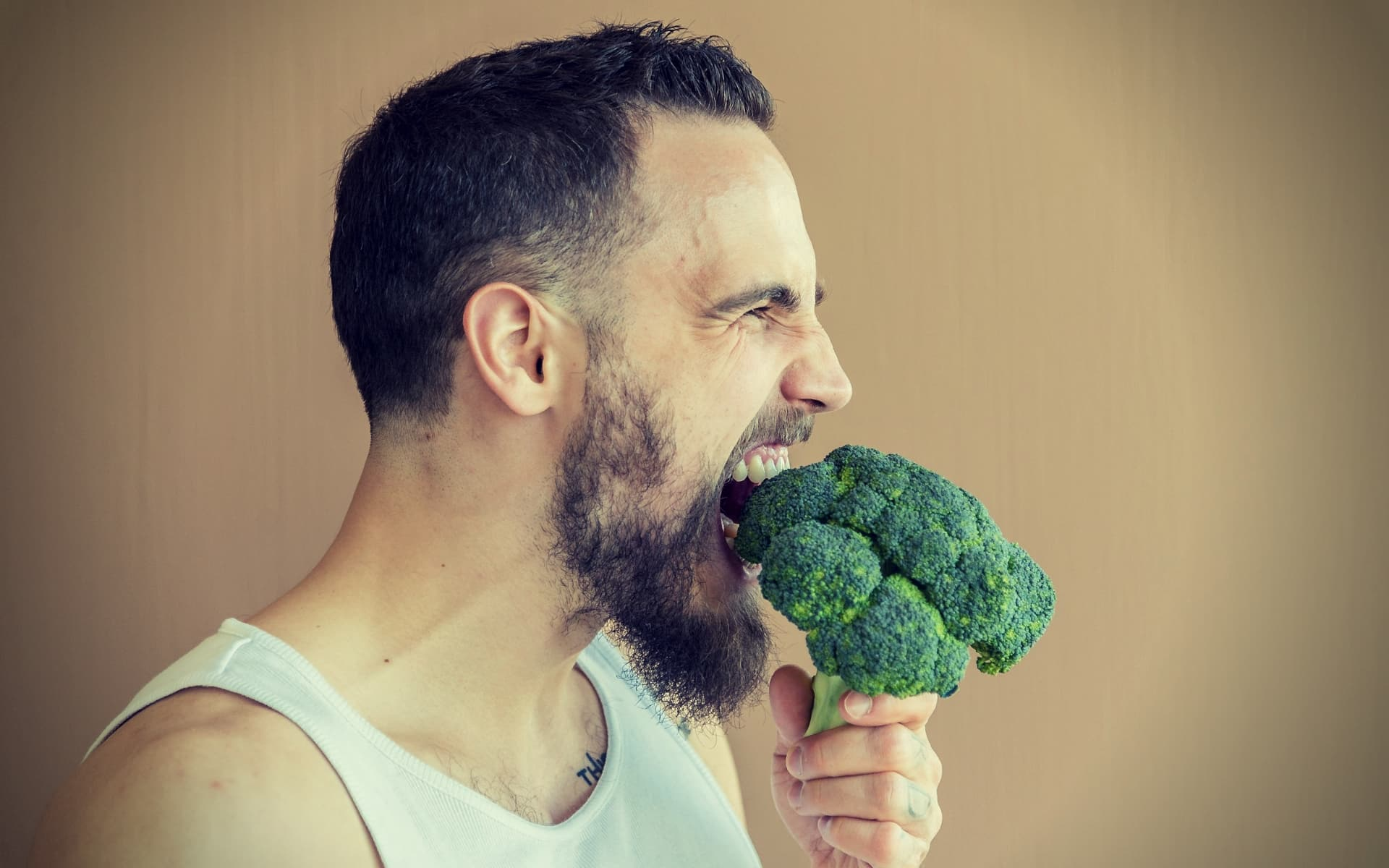 DIM for Men A guy with a beard sniffs broccoli