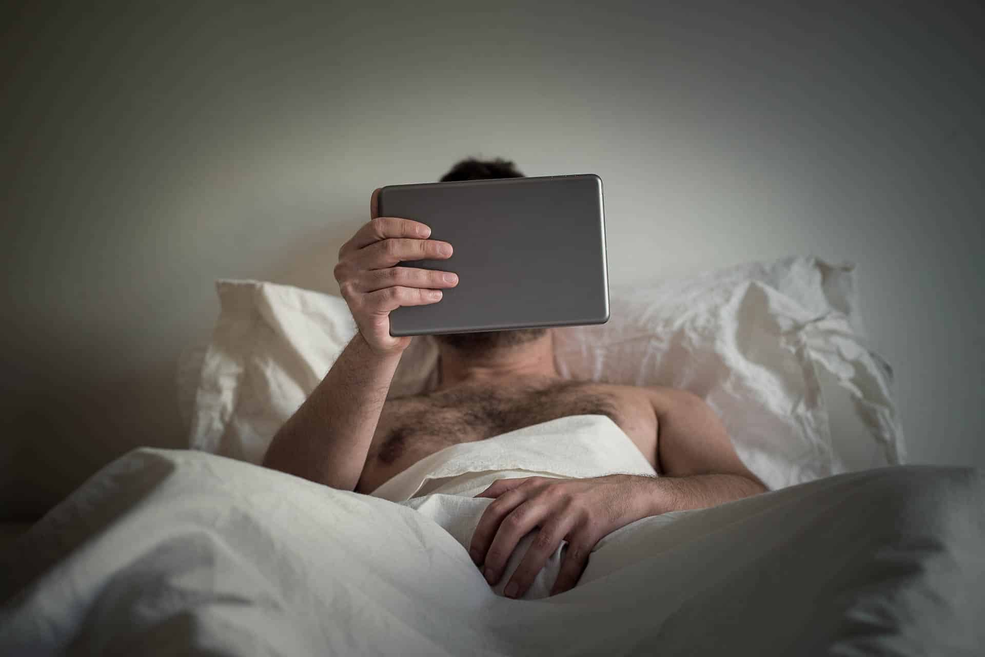 Male Edging man lying on the bed, watching porn on the tablet and masturbate