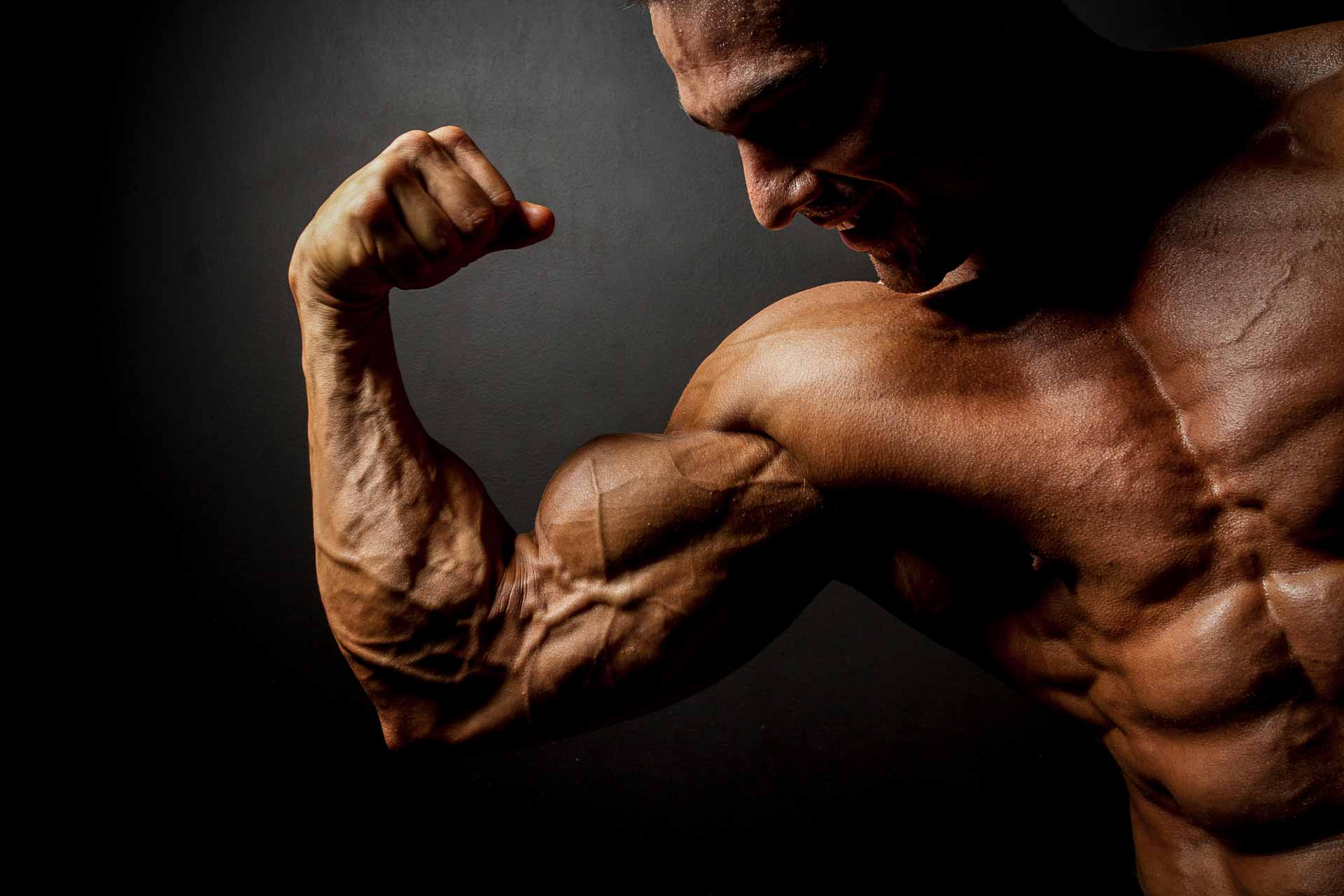 Peptides Bodybuilding strong bodybuilder posing in black background