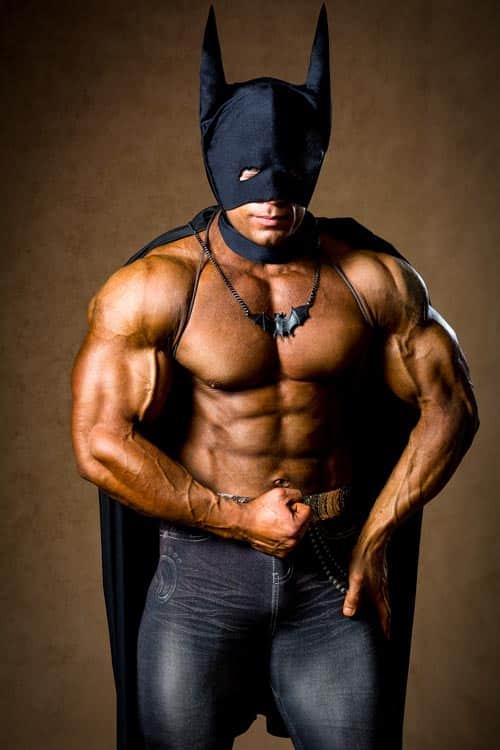 A muscular man in a Batman costume. Hero athlete with strong body