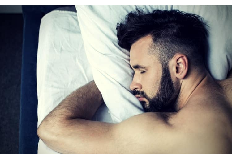 Close-up view of man sleeping in bed