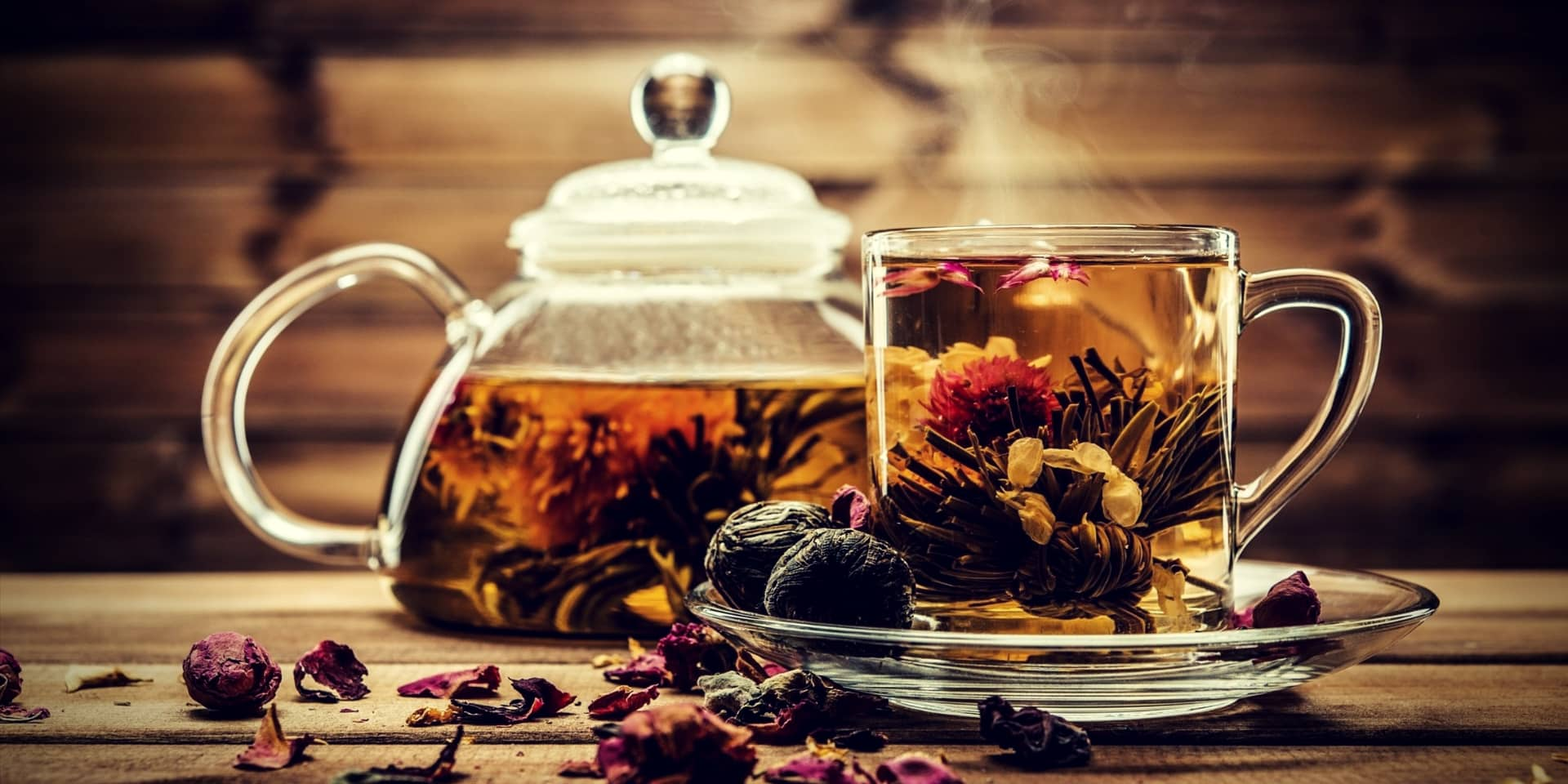 Erection Tea Teapot and glass cup with blooming tea flower inside against wooden background