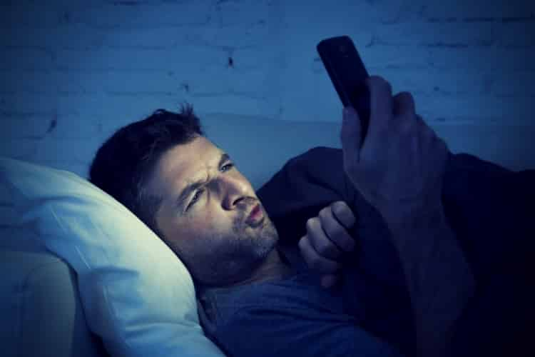 Man in bed couch at home late at night using mobile phone in low light watching online porn
