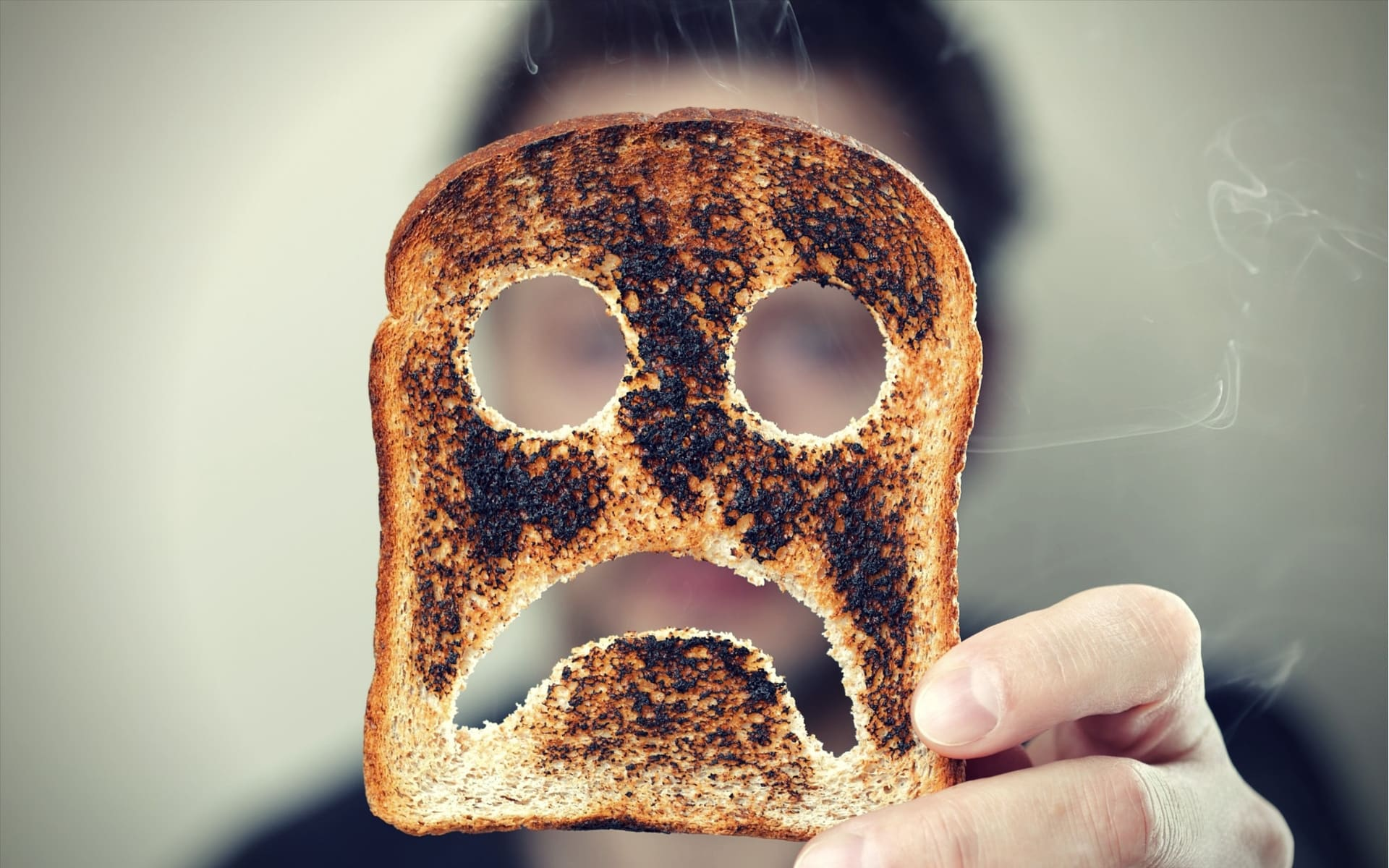 Natural MAO Inhibitors man holding up a burnt slice of toast with an unhappy smiley