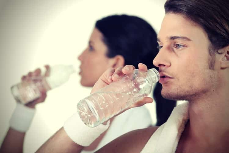 Couple in gym drinking water