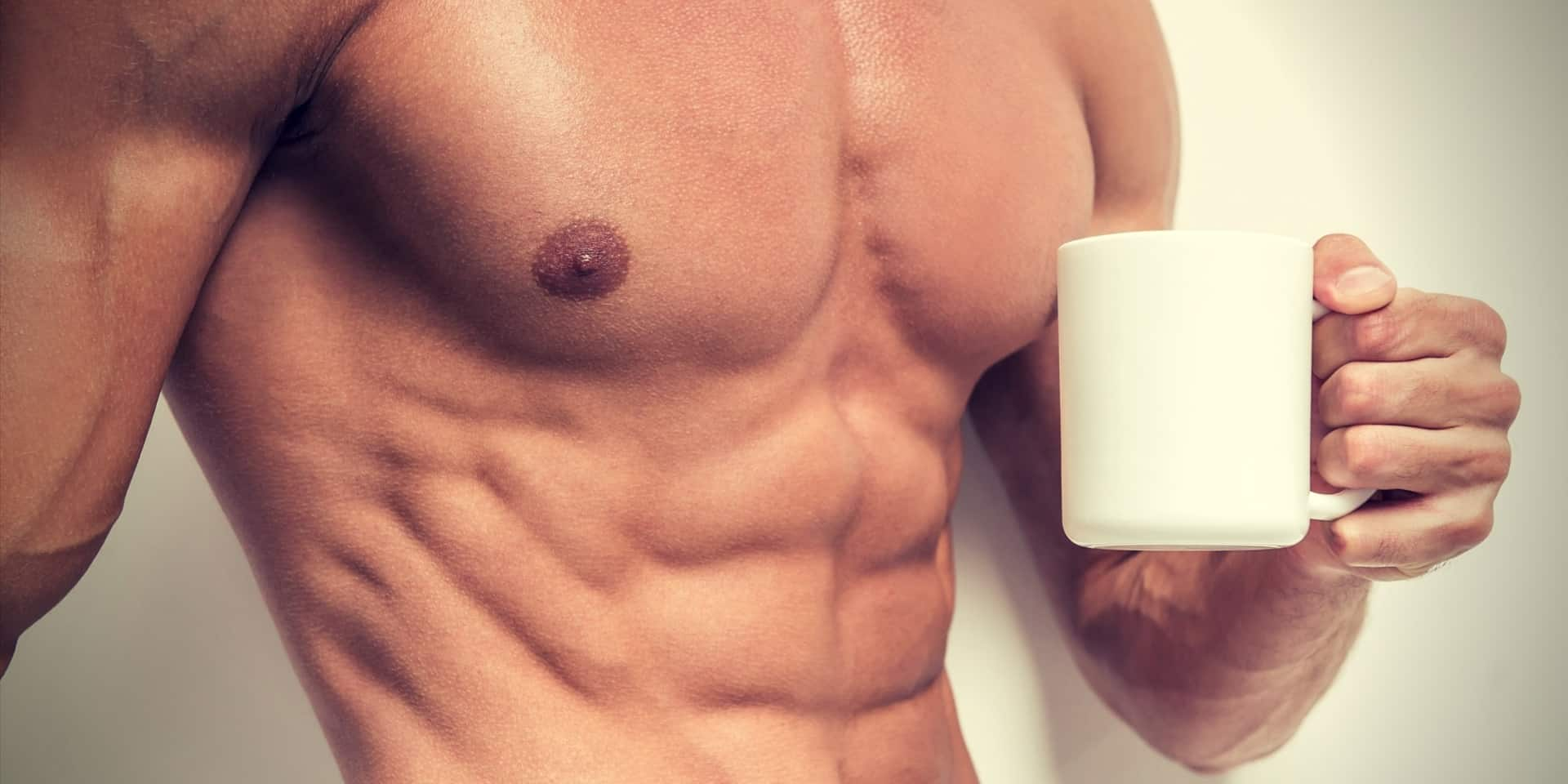 Coffee & Bodybuilding strong man holding a cup of coffee