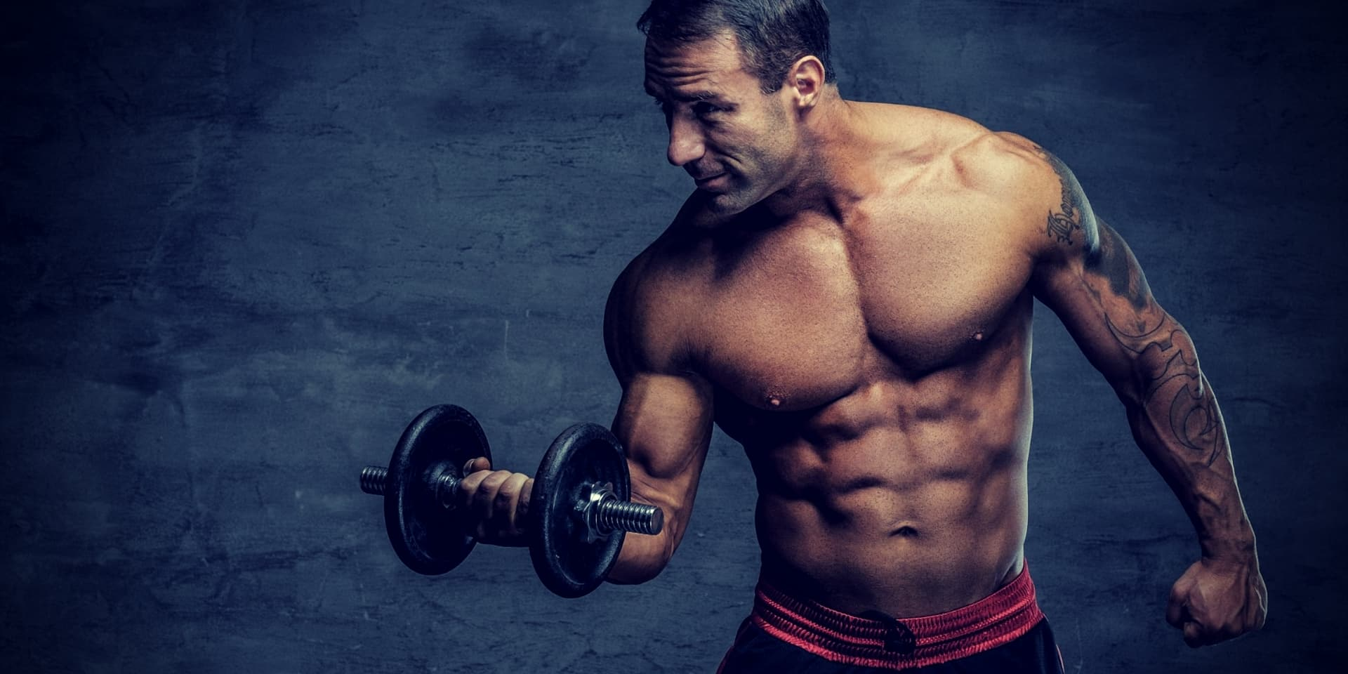 Building Muscle After 40 shirtless middle age man holds dumbbell