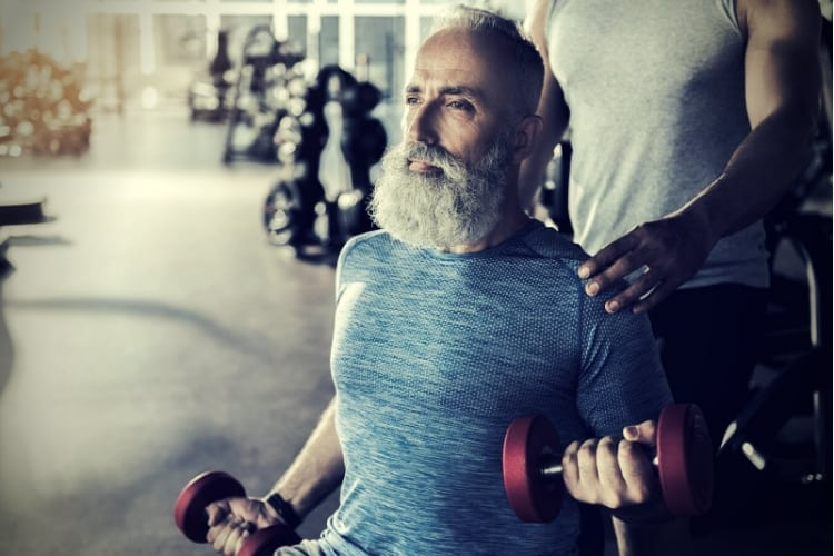 Serious bearded pensioner is doing exercises in athletic center